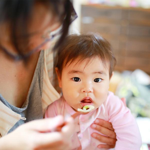 お母さんが赤ちゃんにご飯を食べさせている画像